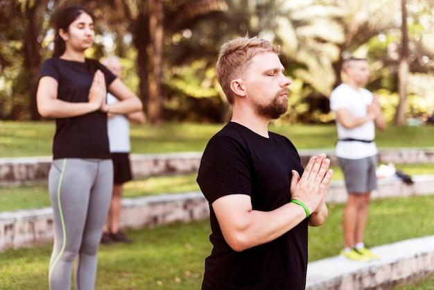 Gente que hace yoga en el parque