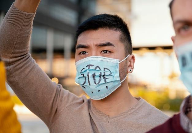 Gente que protesta con máscaras faciales de cerca