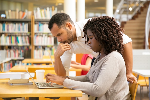 Gente reflexiva que trabaja junto con la computadora portátil en la biblioteca