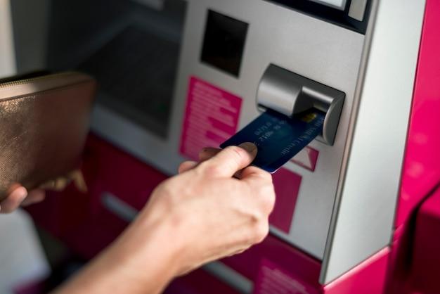 La gente retira dinero usando la máquina