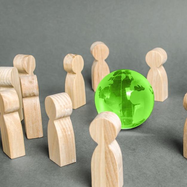 La gente rodeaba un globo terráqueo verde. cooperación y colaboración de personas.