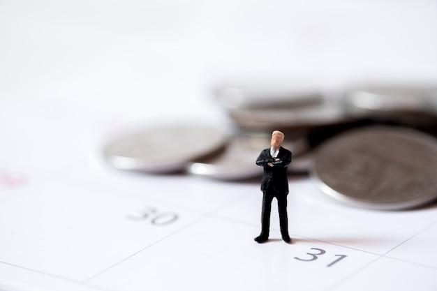 Gente de salario de negocios en miniatura se colocan en la pila de monedas de dinero a fin de mes.