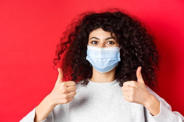 Gente sana y concepto de covid-19. retrato de primer plano de mujer sonriente con cabello rizado, con máscara médica para protegerse durante la pandemia, mostrando el pulgar hacia arriba.