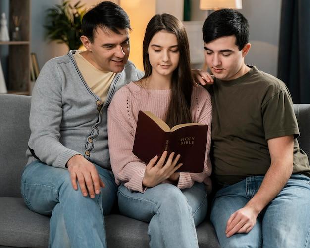 Gente sentada en el sofá y leyendo la biblia.
