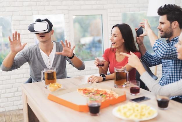 La gente se sienta a la mesa en la que hay vasos de alcohol y comida.