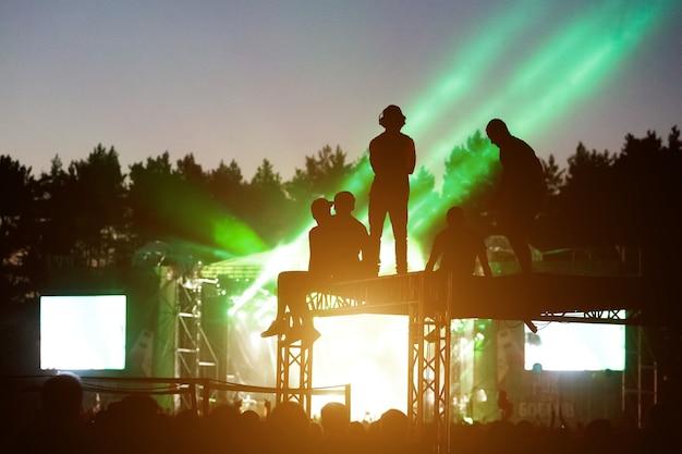 Gente de silueta en festival al aire libre, un concierto en vivo al aire libre