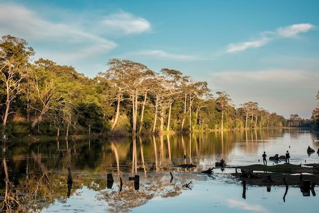 Gente de silueta de pesca en el río y el bosque en el crepúsculo