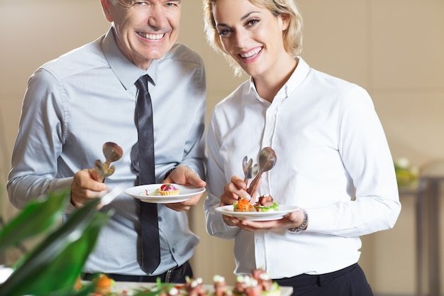 La gente sonríe con los bocados de pie en el buffet