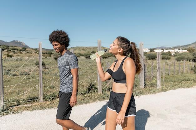 Gente sonriente caminando mientras la mujer bebe agua