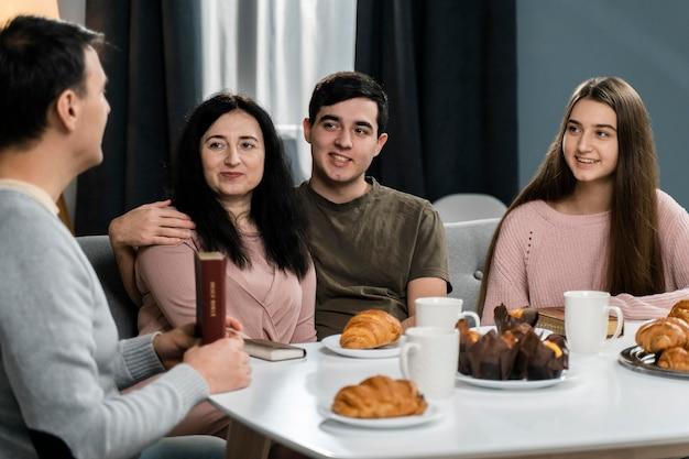 Gente sonriente en la cena con la biblia.