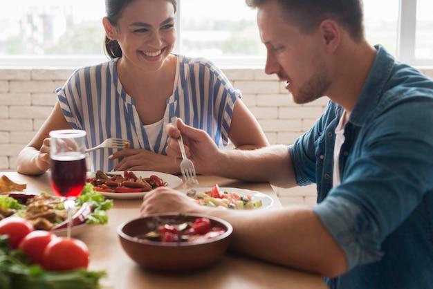 Gente sonriente comiendo juntos