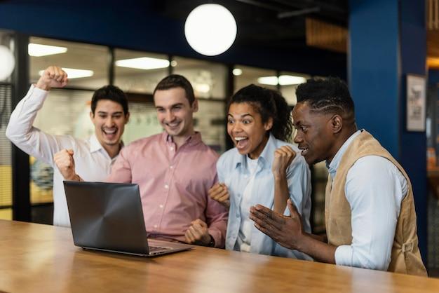 Gente sonriente feliz durante una videollamada en el trabajo