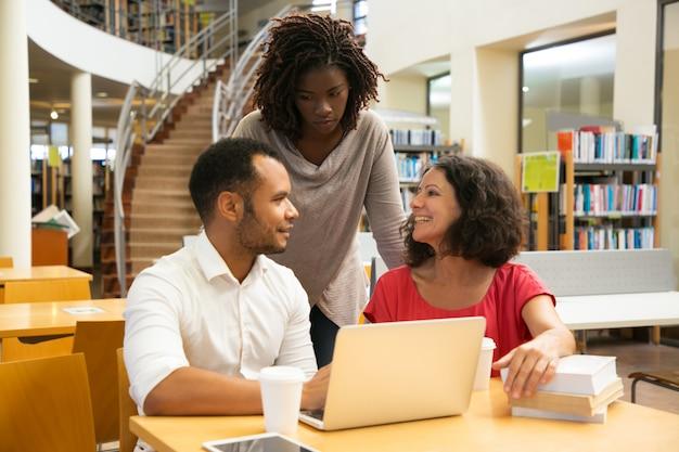 Gente sonriente que se comunica en la biblioteca