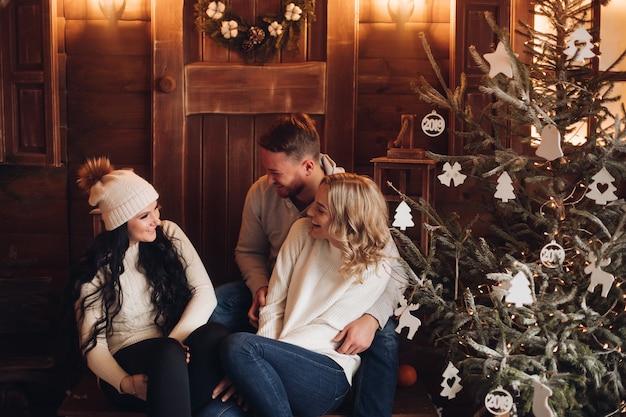 Gente sonriente sentada en el porche de madera delante de la puerta con corona de navidad