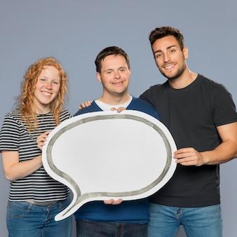 Gente sonriente sosteniendo una burbuja de discurso de papel