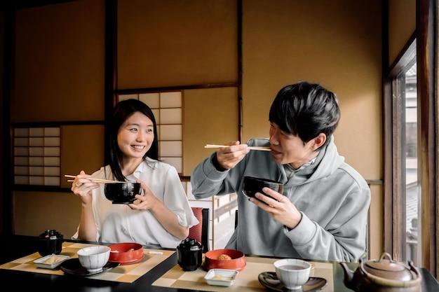Gente sonriente de tiro medio comiendo juntos