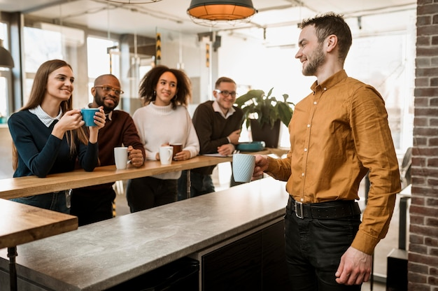 Gente sonriente tomando café durante una reunión