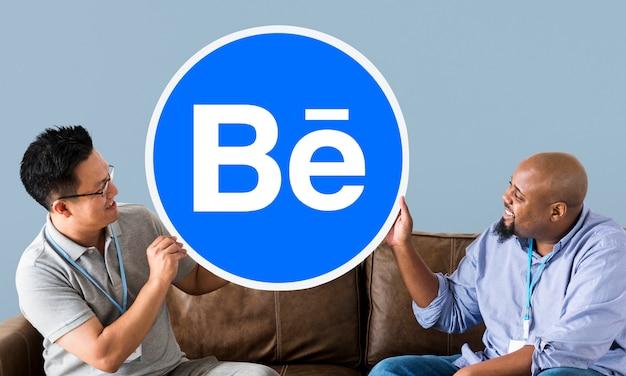 Gente sosteniendo el logo de behance.