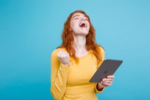 Gente y tecnología concepto - close up retrato joven hermosa atractiva redhair niña feliz sonriendo en la mesa digital con algo ganando. fondo de pastel azul. copie el espacio.