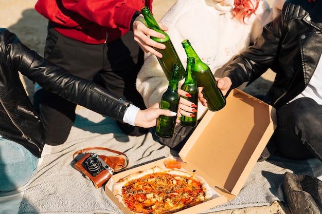 Gente tintineando botellas de cerveza en picnic