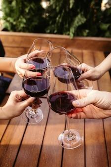 Gente tintineo de vasos con vino en la terraza de verano de cafetería o restaurante. amigos alegres felices celebran el festival de verano u otoño. primer plano de manos humanas, estilo de vida.