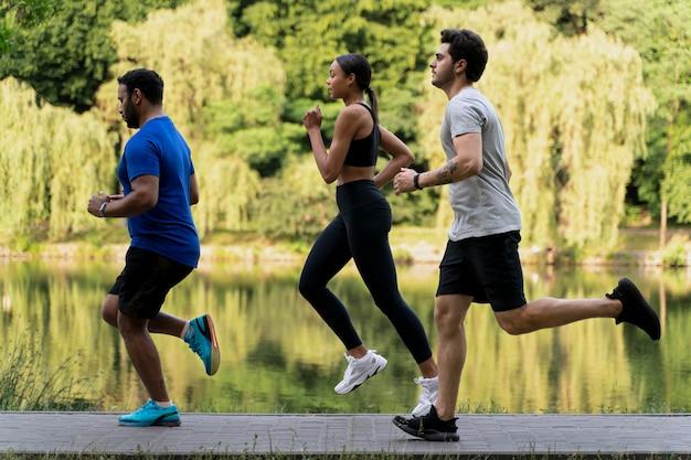 Gente de tiro completo corriendo juntos al aire libre