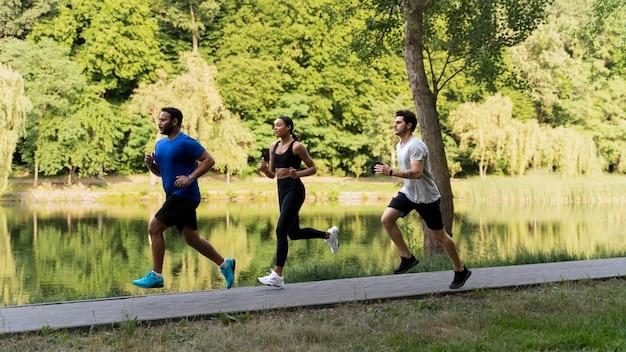 Gente de tiro completo corriendo juntos en la naturaleza
