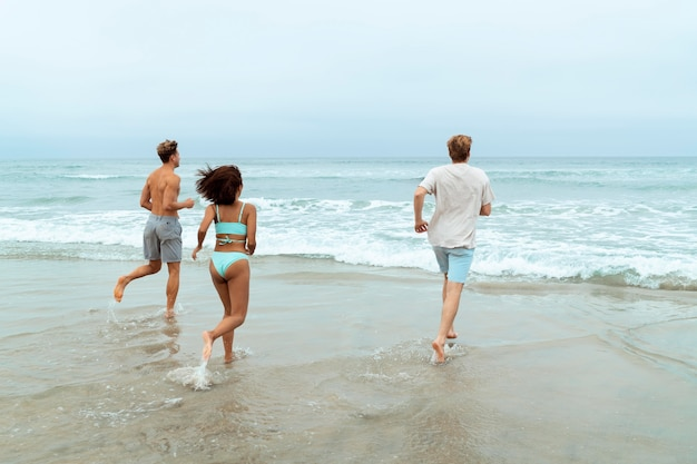 Gente de tiro completo corriendo en la playa