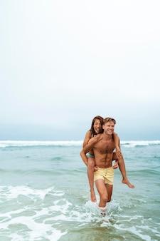 Gente de tiro completo divirtiéndose en la playa