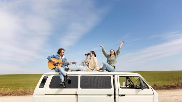 Gente de tiro completo con guitarra en furgoneta