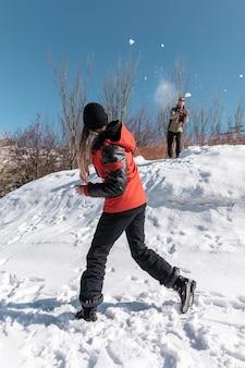 Gente de tiro completo luchando con bolas de nieve