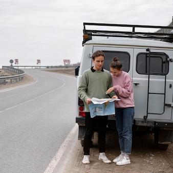 Gente de tiro completo de pie cerca de la furgoneta con mapa