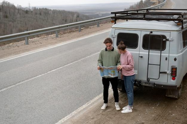 Gente de tiro largo de pie cerca de la furgoneta con mapa