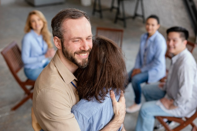 Gente de tiro medio abrazándose en terapia