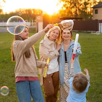 Gente de tiro medio haciendo globos de jabón