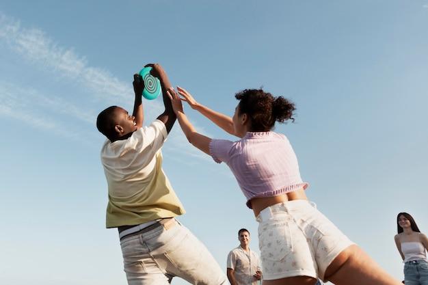Gente de tiro medio jugando en la playa de ángulo bajo
