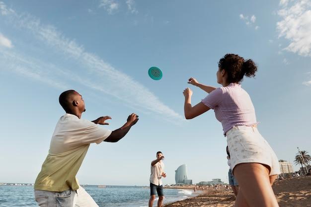 Gente de tiro medio jugando en la playa
