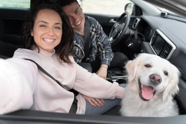 Gente de tiro medio con perro en coche