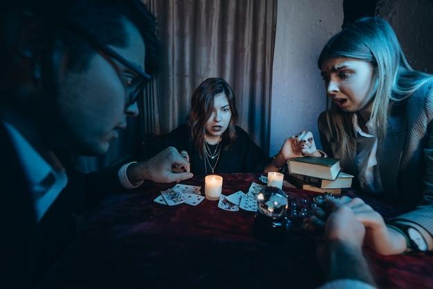 La gente toma las manos de noche en la mesa con velas