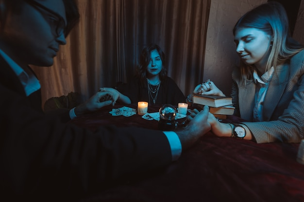 La gente toma las manos de la noche en la mesa con velas