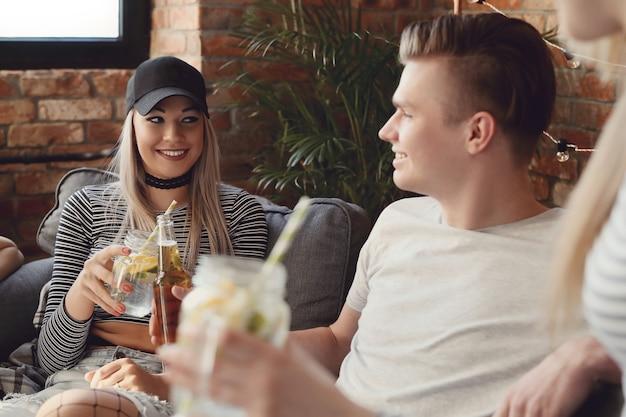 Gente tomando bebidas y celebrando en el bar.