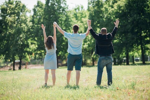 Gente unida de pie y levantando las manos