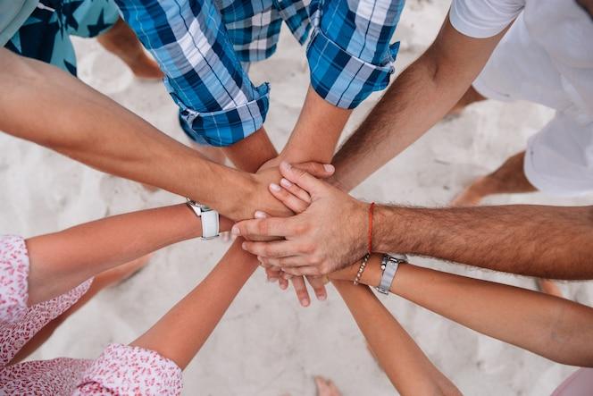 Gente uniéndose manos, grupo de amigos manteniendo las manos juntas.