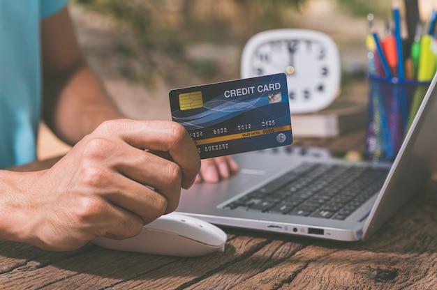 La gente usa tarjetas de crédito para comprar en línea a través de computadoras portátiles.