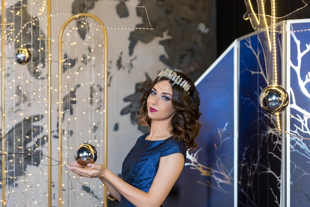 Gente, vacaciones y concepto de moda. feliz joven en vestido azul y corona de princesa en festivo brillante background.portrait de hermosa joven con corona en la cabeza. piel limpia y fresca y