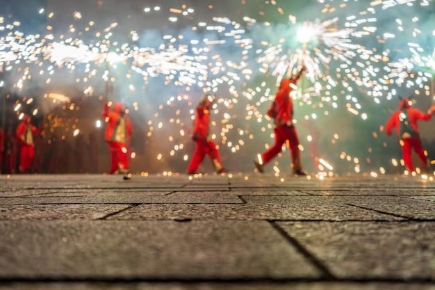Gente vestida como demonios bailando con fuegos artificiales