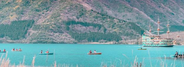 La gente viaja en barcos y barcos en el lago ashi, hakone.