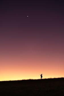 Gente del viaje de la silueta que se coloca en la montaña con el fondo del color de la pendiente del cielo de la puesta del sol.
