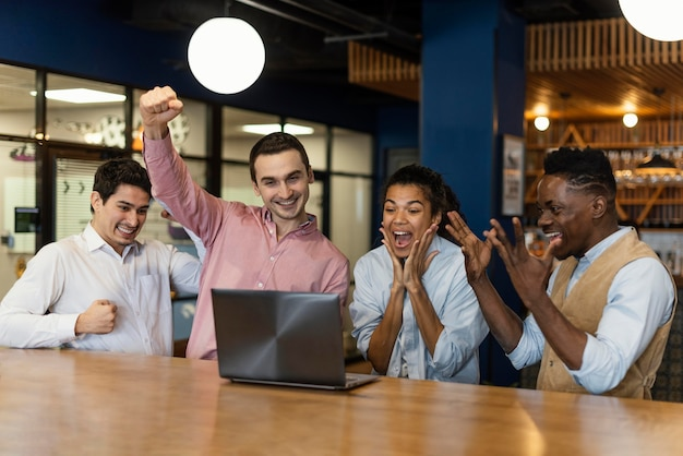 Gente victoriosa siendo feliz durante una videollamada en el trabajo