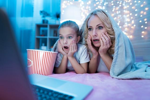 La gente está viendo películas en la computadora portátil en la cama por la noche en su casa.